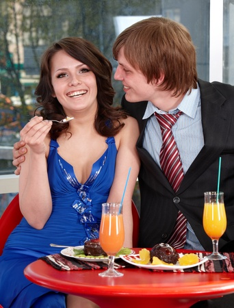 People eating cake in restaurant. Loving couple. photo