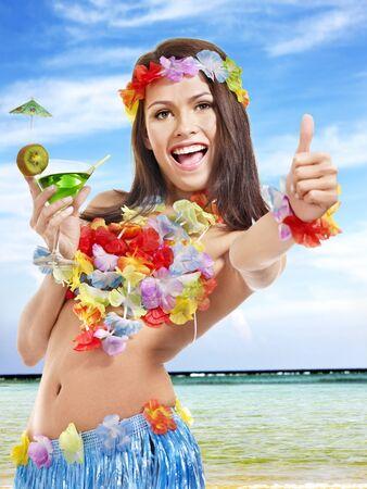 Woman in hawaii costume drink  juice. photo