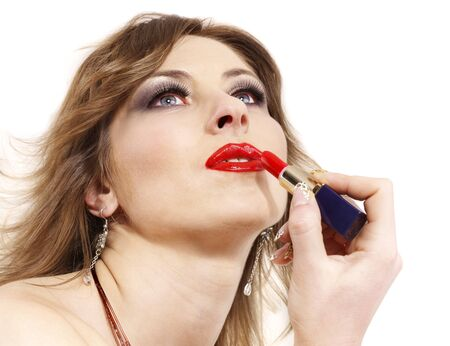 Beautiful woman applying lipstick. Isolated. photo