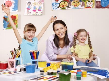 Child painting in preschool. Teacher help by little girl. photo
