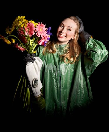 Young woman holding flowers and gas mask . Stock Photo - 9620253