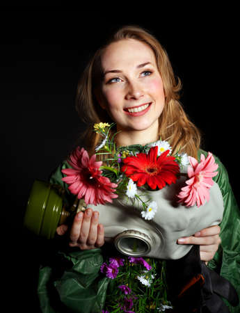 Female hands holding  gas mask with flowers . Stock Photo - 9620270