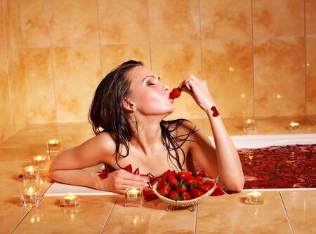 Woman relaxing in bath with rose petal. photo