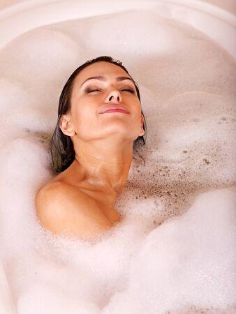 femme baignoire: Femme relaxante dans un bain moussant.