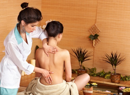 Young woman getting massage in bamboo spa.. photo