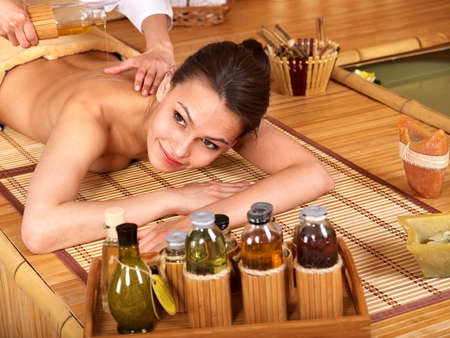 Young woman getting massage in bamboo spa. Stock Photo - 9620324
