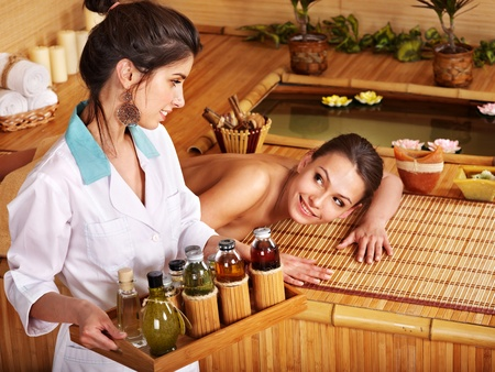 Young woman getting massage in bamboo spa. Stock Photo - 9620328