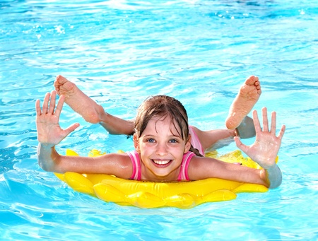 float tube: Children  on inflatable ring in swimming pool.