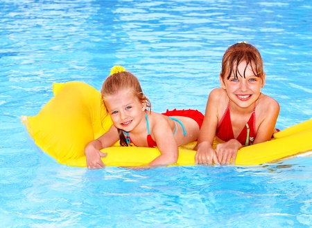 kids playing water: Children swimming on inflatable beach mattress. Stock Photo