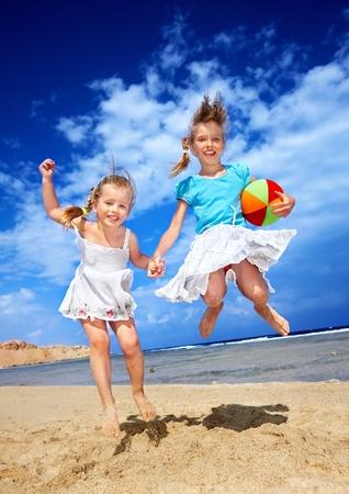 klein meisje op strand: Meisje spelen op het strand met bal.