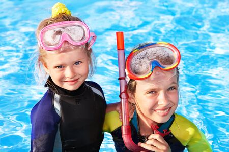 Children in swimming pool learning snorkeling. Sport. photo