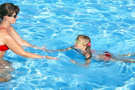 Swimming instructor learn little girl swim. photo