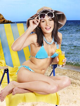 deck chair: Girl in bikini drink juice through a straw on beach. Stock Photo