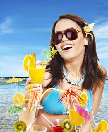 Girl in bikini on beach drinking cocktail. Stock Photo - 9780460