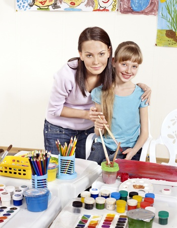 maestra preescolar: Pintura infantil en edad preescolar. Maestro ayudar ni?a. Foto de archivo