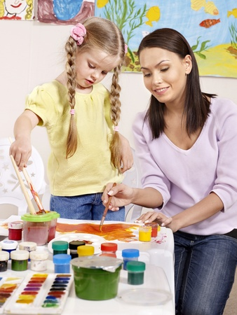 child care: Happy child painting in preschool.