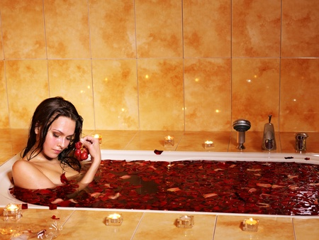 Woman swimming of bath tub.