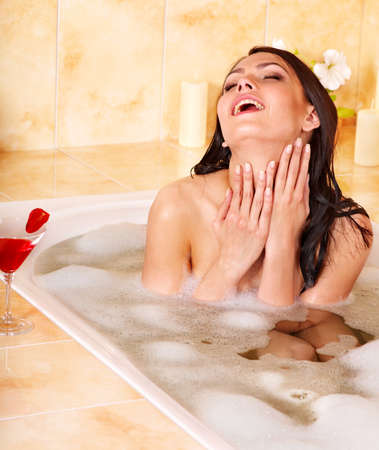 Woman washing in bubble bath. photo