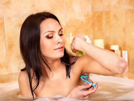 Young woman shaving her body in  bath. photo