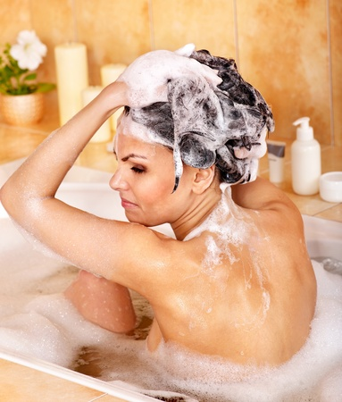 washing hair: Woman washing hair in bubble bath. Stock Photo