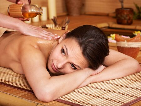 Young woman getting massage in bamboo spa. Stock Photo - 9780569