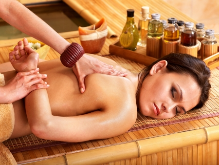 massage therapy: Young woman getting massage in bamboo spa.