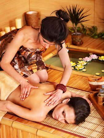 Young woman getting massage in bamboo spa. Stock Photo - 9780762