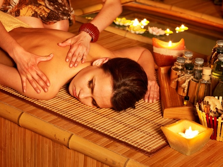 Young woman getting massage in bamboo spa. Stock Photo - 9780120