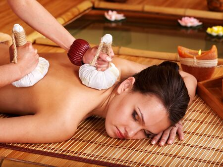 Young woman getting massage in bamboo spa. Stock Photo - 9780758