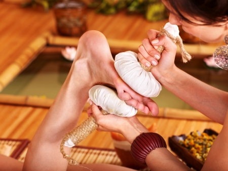 Young woman getting foot massage in bamboo spa. Stock Photo - 9779840