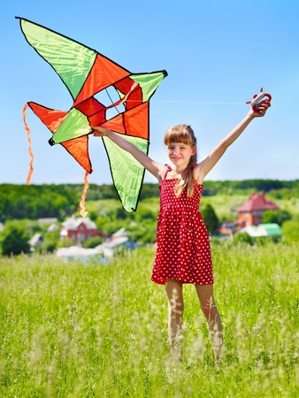 kite flying: Child flying kite outdoor. little girl running across  green grass.