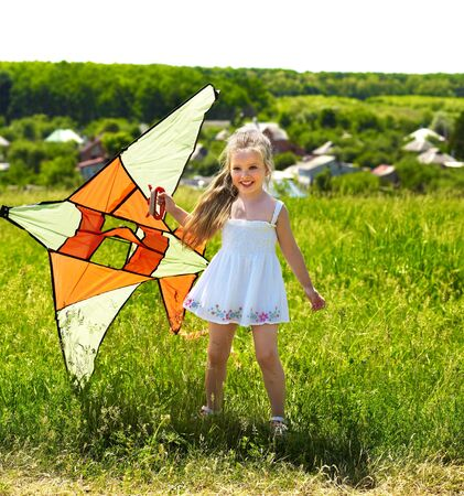 flying a kite: Child flying kite outdoor. little girl running across  green grass.