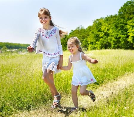 Group children running across green grass outdoor.  photo