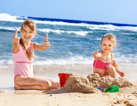 sandcastles: Thumb up children playing on  beach.  Stock Photo
