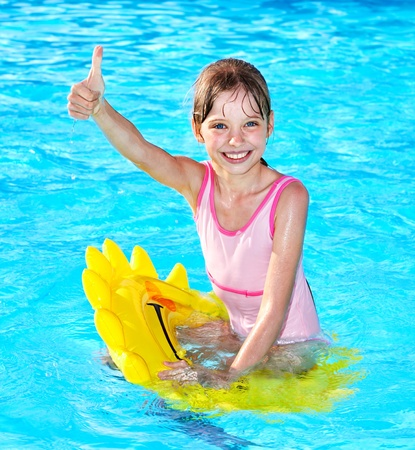 one piece swimsuit: Children sitting on inflatable ring in swimming pool. Stock Photo