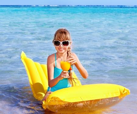 Little girl swimming on inflatable beach mattress. photo
