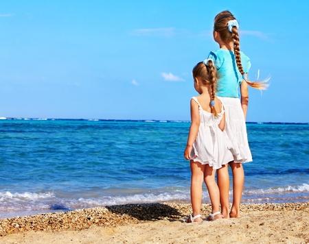 enfant maillot: Enfants tenant par la main de marcher sur la plage. Vue arri�re.