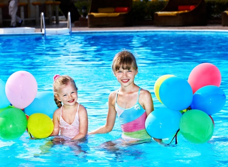 children party: little girl playing with balloons in swimming pool.