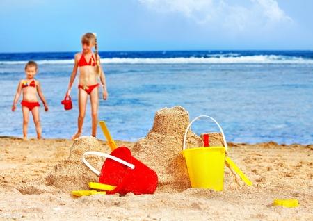seau d eau: Petite fille jouant sur la plage avec ballon.