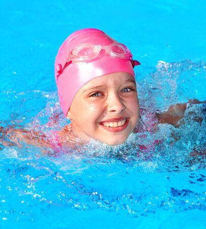 cap: Little girl  swimming in pool. Stock Photo