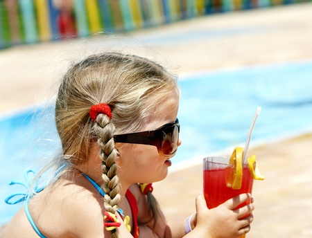Little girl in glasses and red bikini on playground drink  juice. Stock Photo