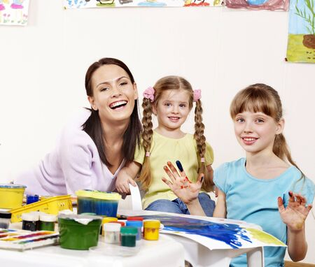 Children painting in preschool. Teacher help by little girl. Stock Photo - 9793986