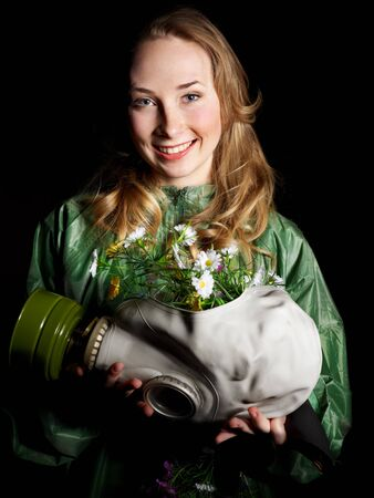 Young woman holding flowers and gas mask . Stock Photo - 9780985