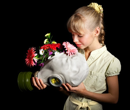 Little girl holding flowers and gas mask . Stock Photo - 9781163