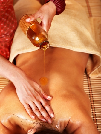 oil massage: Young woman getting massage in bamboo spa.