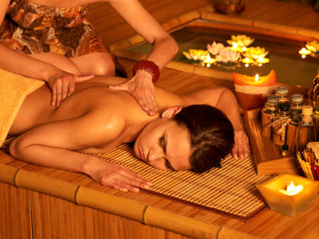 wooden aromatherapy: Young woman getting massage in bamboo spa.