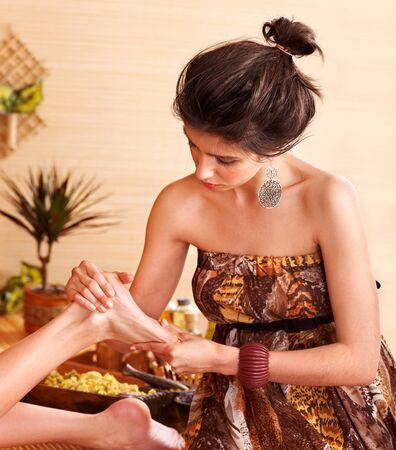 massage oil: Jeune femme se massage des pieds dans le spa de bambou.