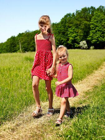 ni�os caminando: Agrupe a los ni�os caminando a trav�s de la hierba verde al aire libre.