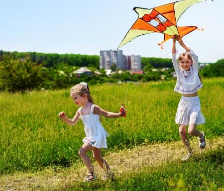 wellness environment: Group children flying kite outdoor.