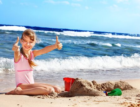bucket and spade: Thumb up child playing on  beach.